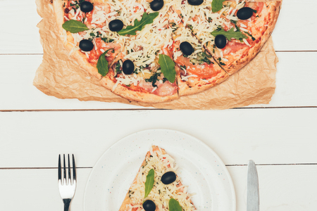 Pizza slice served on white plate on white wooden background