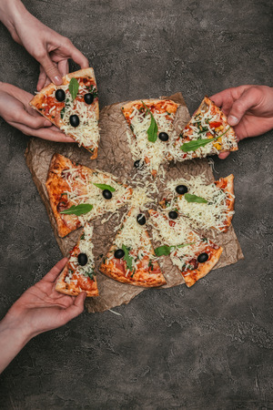 Close-up view of people eating pizza on dark background Banco de Imagens