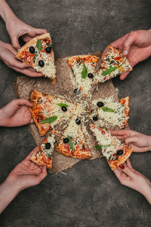 Close-up view of people taking slices of pizza on dark background Banco de Imagens