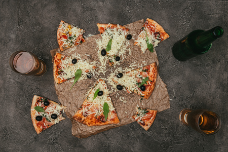 Slices of pizza and drink on dark background