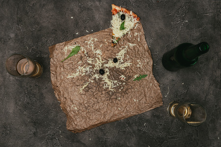 Pizza leftovers on craft paper with beer on dark background Stock Photo - 99246143