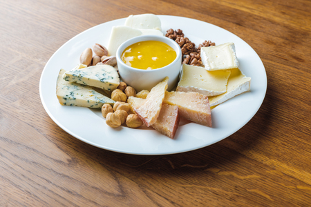close-up view of delicious cheese plate with nuts and honey o