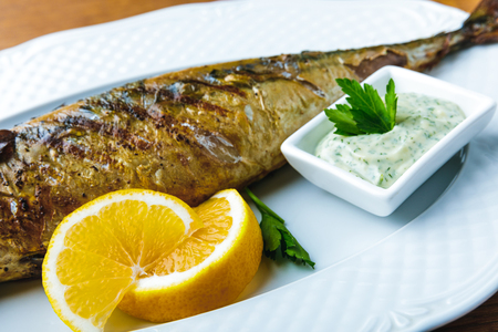 delicious grilled mackerel with sauce and lemon slices