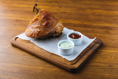 close-up view of gourmet roasted pork knuckle with sauces Stock Photo