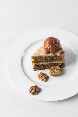 Cake on white plate surrounding by walnuts