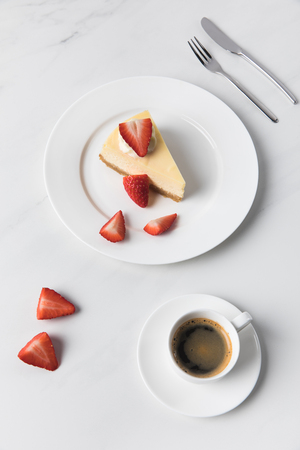 Coffee cup with cheesecake and sliced strawberries