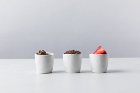 three bowls with walnuts, grated chocolate and strawberries