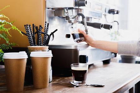 Close-up view of barista preparing coffee on modern espresso machine
