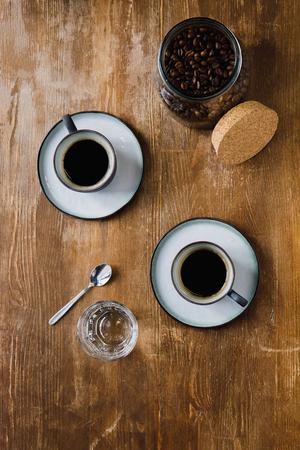 木製のテーブルの上の瓶にブラックコーヒーとコーヒー豆の2カップ