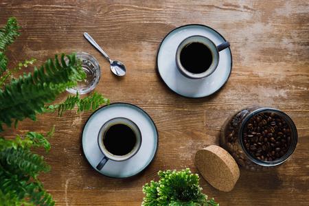 コーヒーショップの植物とテーブルの上のカップに朝のブラックコーヒー 写真素材