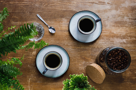 Morning black coffee in cups on table with plants in coffee shop Stock Photo
