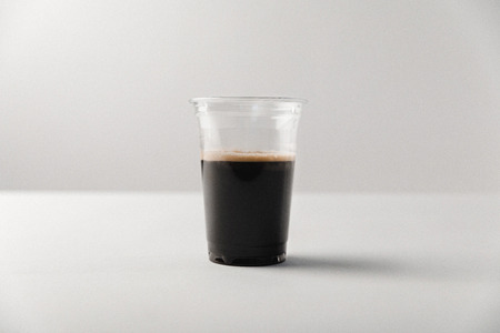 Disposable cup with black coffee on white background Stock Photo