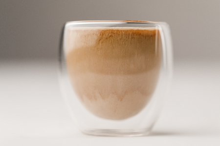 Glass cup filled with coffee with milk on white background Stock Photo