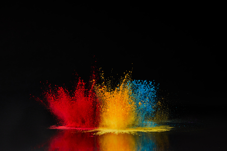 red, blue and yellow holi powder explosion on black, Hindu spring festival