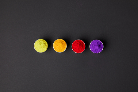 top view of row of colorful holi paint in bowls on grey surface