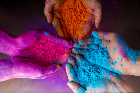 hands with holi powder for Hindu spring festival of colours