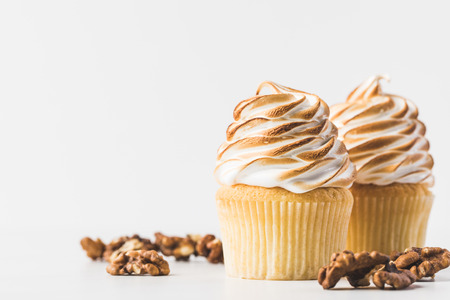 close up view of sweet cupcakes with meringue isolated on white Banco de Imagens