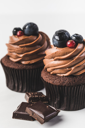 close up view of chocolate cupcakes with cream, grape, berries and pieces of chocolate isolated on white