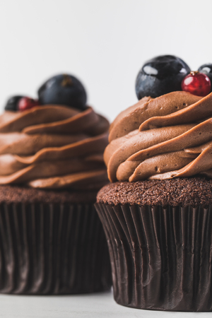 chocolate cupcakes with cream, grape and berries isolated on white