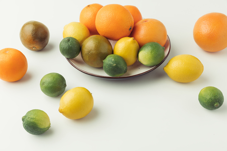 Raw citruses on plate on white background