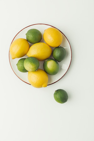 Top view of lemons and limes on plate isolated on white background