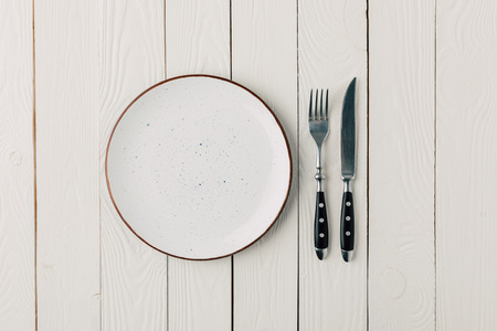 Empty plate and cutlery on white wooden background