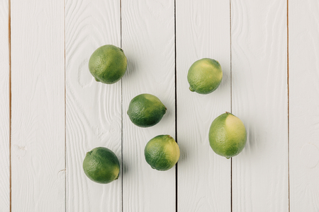 Greek limes on white wooden background 写真素材