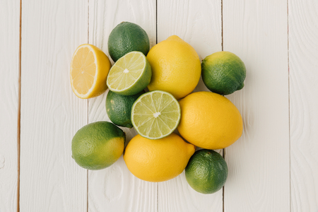 top view of citrus fruits on white wooden background