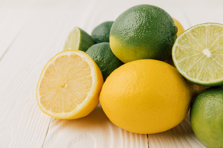 Green limes and yellow lemons on white background