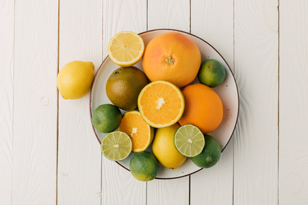 Juicy sour citruses on plate on white background