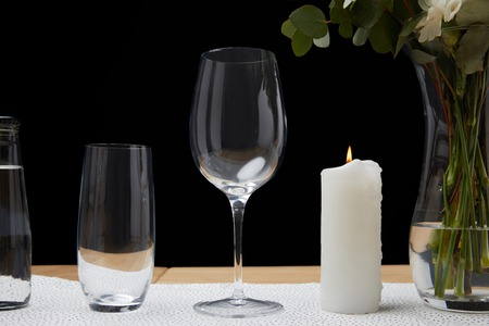 Tender flowers in vase with water bottle and empty glasses on table next to candle