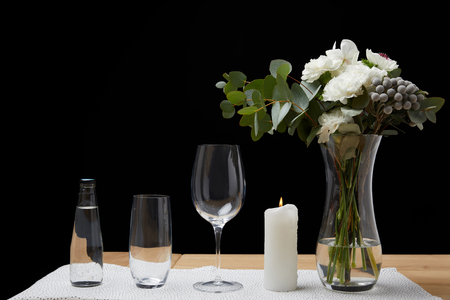 Bouquet in vase with water bottle and empty glasses on table next to candle