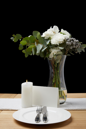 Flowers in vase with cutlery and plate on table next to blank card
