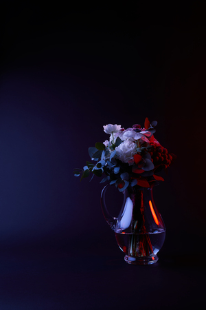 bouquet of different flowers in glass carafe with water