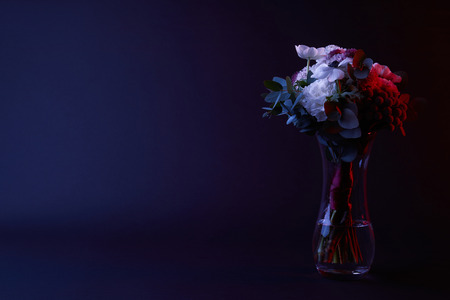 bouquet of different flowers in glass vase with red light Banco de Imagens