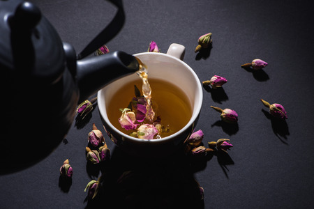 pouring tea from black kettle into cup and dry pink rose buds on black