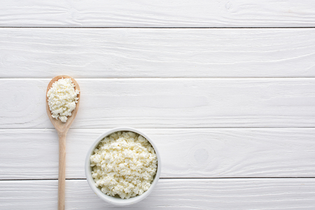 fresh healthy cottage cheese in bowl and wooden spoon on table
