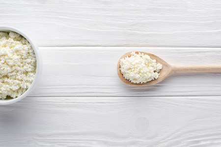 top view of fresh healthy cottage cheese in bowl and wooden spoon on table