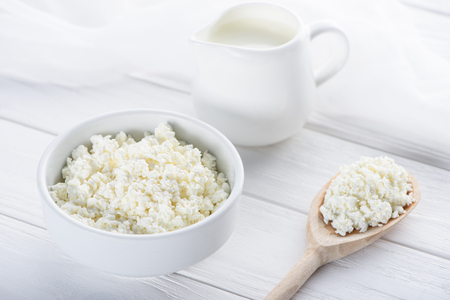 close-up view of fresh healthy cottage cheese, wooden spoon and milk in jug on wooden table Stock Photo