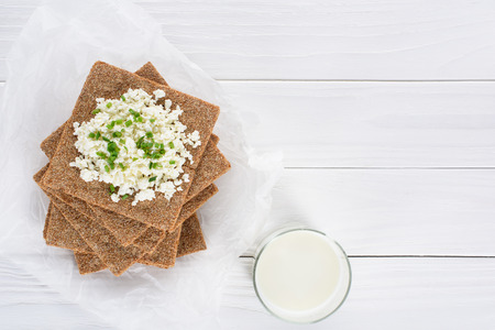 top view of glass of milk and crackers with cottage cheese on wooden table