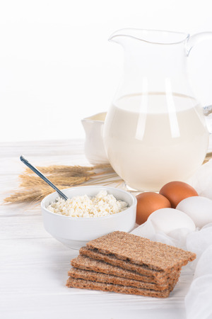 close-up view of crispy crackers, eggs, milk and cottage cheese on wooden table  Stock Photo