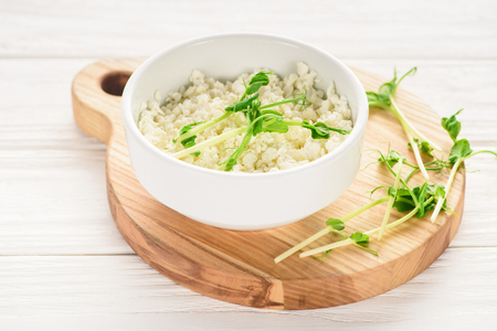 close-up view of bowl with fresh healthy cottage cheese with sprouts on wooden board