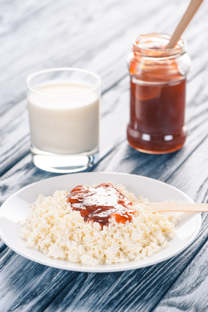 close-up view of delicious cottage cheese with jam and glass of milk on wooden table  写真素材