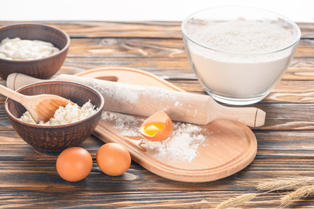 close-up view of cottage cheese, eggs and flour on wooden table