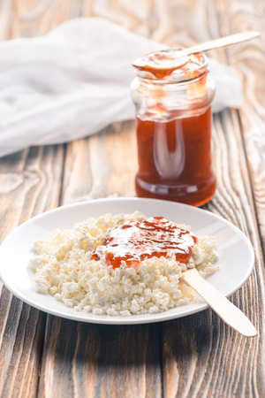 close-up view of tasty healthy cottage cheese with jam on wooden table