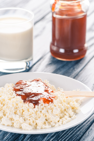 close-up view of healthy cottage cheese with jam and glass of milk on table