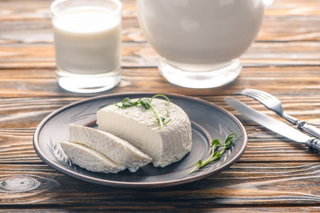close-up view of tasty healthy soft cheese on plate and glass of milk on wooden table Stock Photo