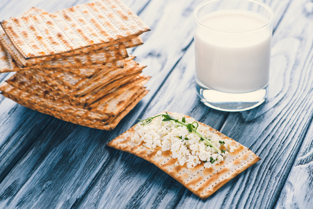 close-up view of crackers with cottage cheese and glass of milk on wooden table