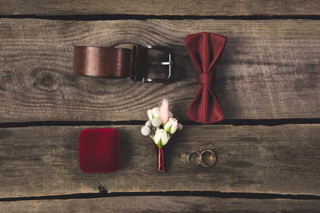 flat lay with arranged grooms accessories and wedding rings on wooden tabletop
