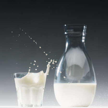 Glass of milk with splashes in front of milk bottle